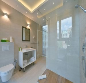wetroom with soft colour tiled and glass shower in Hamilton